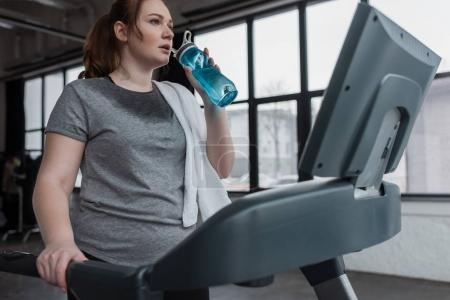 Photo for Curvy girl drinking from water bottle while running on treadmill in gym - Royalty Free Image