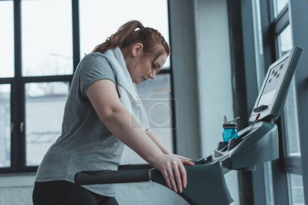 Obese girl resting on treadmill in gym