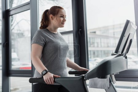 Photo for Obese girl running on treadmill in gym - Royalty Free Image