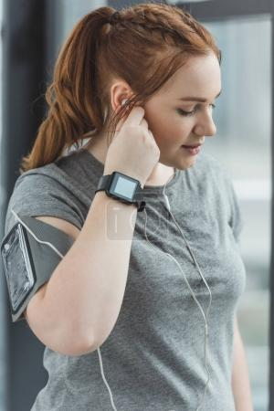 Curvy girl with fitness tracker listening to music in gym