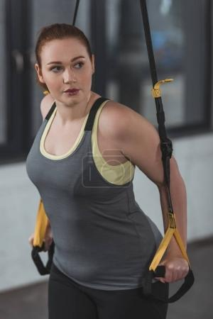 Overweight girl training on suspension straps in gym
