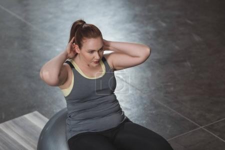 Curvy girl exercising on fitness ball in gym