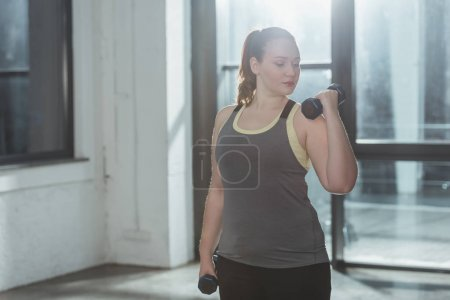 Photo for Curvy girl lifting dumbbells in gym - Royalty Free Image