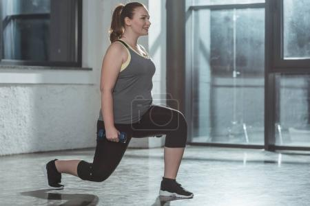 Overweight girl performing lunges with dumbbells in gym