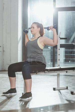 Obese girl lifting dumbbells in gym