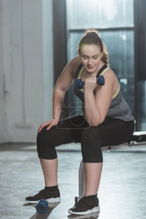 Overweight girl training with dumbbell in gym