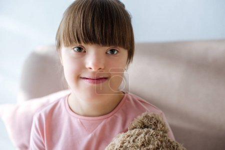 Kid with down syndrome sitting on sofa with teddy bear toy