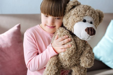 Kid with down syndrome sitting on sofa and hugging teddy bear