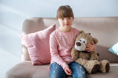 Photo pour Enfant avec le syndrome du duvet assis sur le canapé et étreignant ours en peluche - image libre de droit