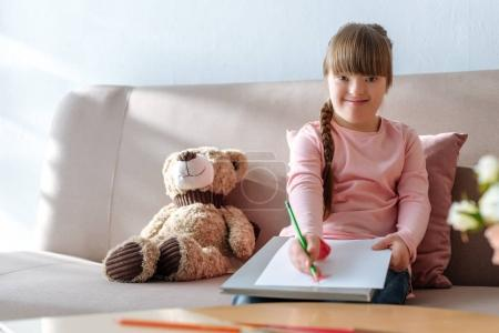 Smiling kid with down syndrome drawing with colorful pencils