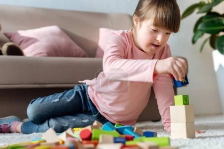 Enfants atteints de mongolisme, jouant avec des cubes de jouet étage dans la chambre au confort douillet