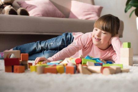 Photo pour Enfant avec le syndrome du duvet couché sur le sol et regardant des cubes de jouets - image libre de droit