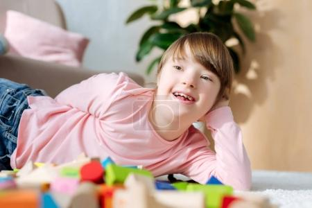 Child with down syndrome lying on floor with toy cubes