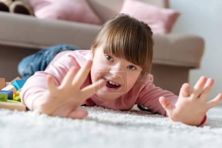 Photo pour Enfant heureux avec le syndrome du duvet couché sur le sol dans une chambre confortable - image libre de droit