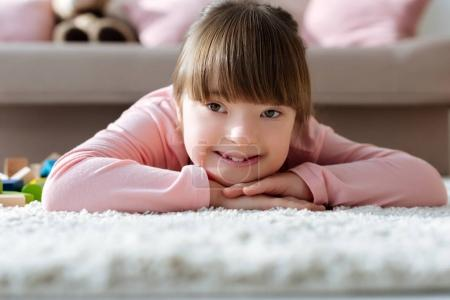 Smiling kid with down syndrome lying on floor