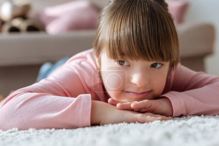 Dreamy child with down syndrome lying on floor in cozy room