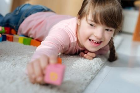 Photo for Child with down syndrome holding toy cube - Royalty Free Image