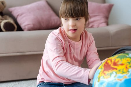 Kid with down syndrome playing with globe