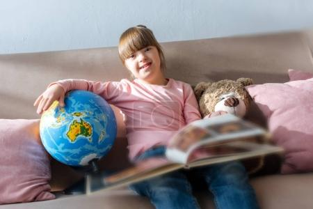 Child with down syndrome reading book and playing with globe