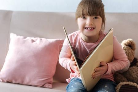 Photo pour Rire enfant avec le livre de lecture du syndrome du duvet - image libre de droit