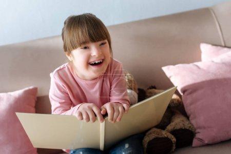 Photo pour Enfant atteint du syndrome du duvet tenant le livre et riant - image libre de droit