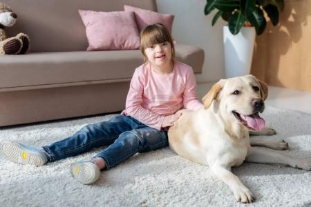 Kid with down syndrome sitting on the floor with Labrador retriever on carpet