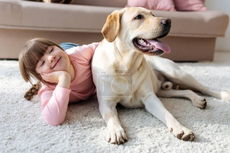 Happy child with down syndrome lying on the floor with Labrador retriever