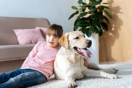 Child with down syndrome hugging Labrador retriever on the floor
