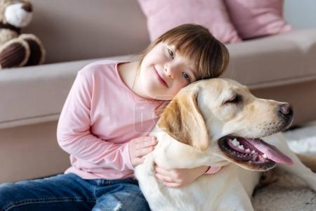 Photo pour Enfant atteint du syndrome du duvet câlins avec chien - image libre de droit