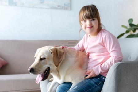 Kid with down syndrome and Labrador retriever sitting in chair