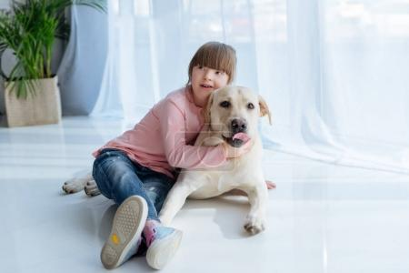 Child with down syndrome embracing Labrador retriever lying on the floor