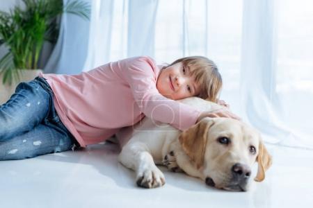 Photo pour Enfant heureux avec le syndrome du duvet et Labrador retriever câlins sur le sol - image libre de droit