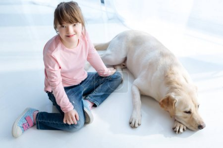 Top view of child with down syndrome and dog retriever in room