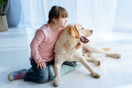 Photo for Child with down syndrome and Labrador retriever looking aside in one direction - Royalty Free Image