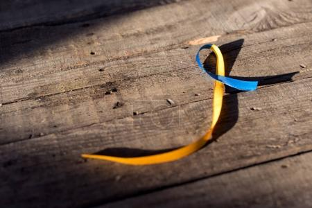 Photo for Blue and yellow ribbon on wooden background for Down Syndrome Day background - Royalty Free Image