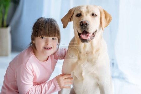 Photo for Happy child girl with down syndrome cherishing Labrador retriever - Royalty Free Image