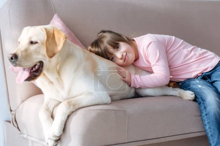 Kid with down syndrome lying on the sofa with Labrador retriever dog