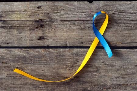 Photo for Down Syndrome Day blue and yellow ribbon on wooden background - Royalty Free Image