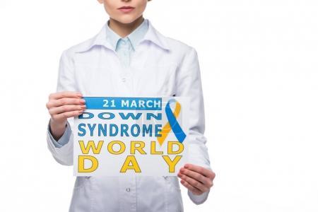 Photo pour Jeune médecin tenant signe avec la journée mondiale de la trisomie isolé sur blanc - image libre de droit