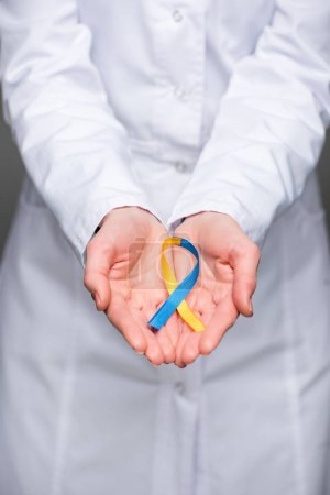 Photo for Female doctor hands holding Down Syndrome Day symbol blue and yellow ribbon - Royalty Free Image