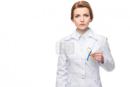 Photo for Doctor holding blue and yellow ribbon for Down Syndrome campaign isolated on white - Royalty Free Image