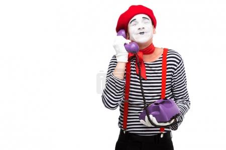 Photo for Happy mime talking by retro stationary telephone with closed eyes isolated on white - Royalty Free Image