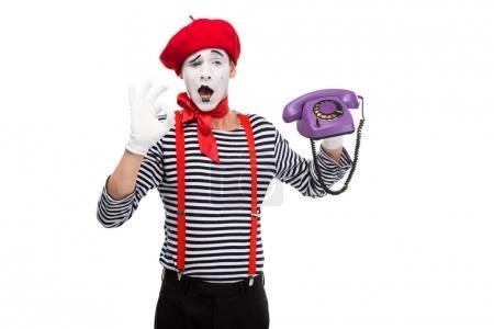 Photo pour Mime tenant le téléphone stationnaire ultra violet rétro et montrant ok signe isolé sur blanc - image libre de droit