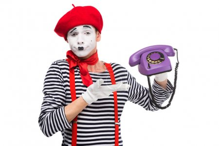 skeptical mime showing at ultra violet retro stationary telephone isolated on white