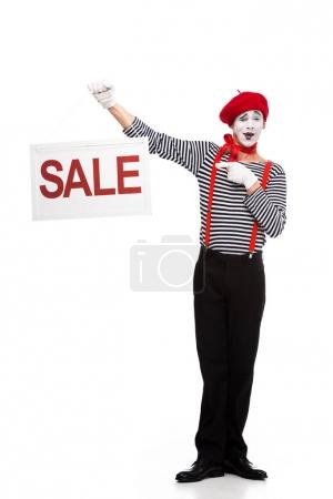 happy mime pointing on sale signboard isolated on white