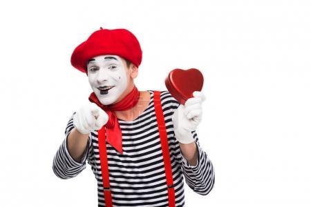 Photo pour Mime tenant boîte cadeau en forme de coeur et pointant sur la caméra isolé sur blanc, st concept de Saint-Valentin - image libre de droit