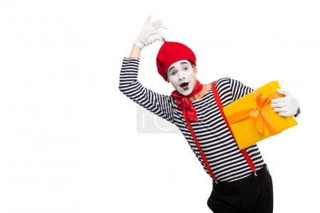 Photo for Surprised mime holding gift box and touching red cap isolated on white - Royalty Free Image