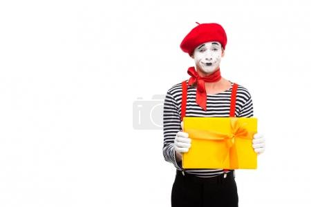 grimacing mime showing gift box isolated on white