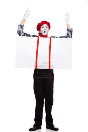 grimacing mime holding empty board under suspenders with hands up isolated on white