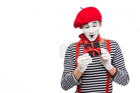 surprised mime looking at present box isolated on white